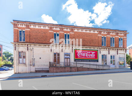 STATESVILLE, NC, USA-1 SEPTEMBER 2019: An old commercial building in down town, with Coca-cola ad, and sign saying 'Welcome to Historic Statesville'. - Stock Photo