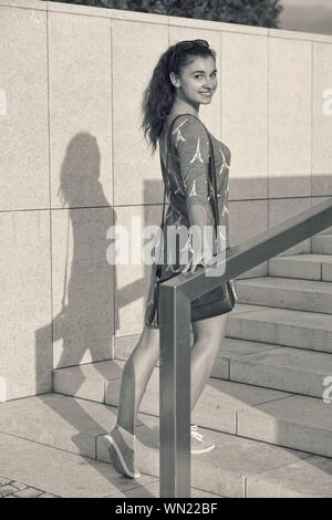 Beautiful Woman Wearing Dress With Eiffel Tower Pattern Walking On Steps During Sunny Day - Stock Photo