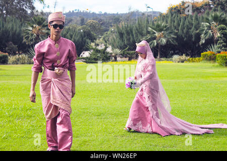 Confident Bride And Groom In Traditional Clothing Walking On Grassy Field