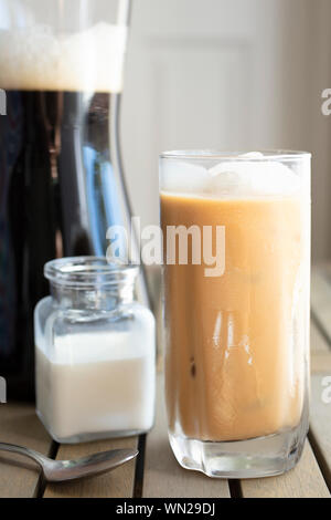 A glass filled with cold brew coffee with cream and ice near the pitcher on a kitchen table - Stock Photo