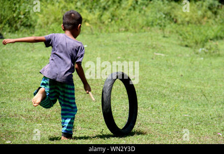 Rear View Of Boy Playing With Tire On Field - Stock Photo