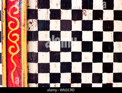 Cabinet doors given a decorative paint job with black and white checks and yellow and red borders. - Stock Photo
