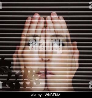 Double Exposure Of Woman Face With Hands Against Blinds - Stock Photo