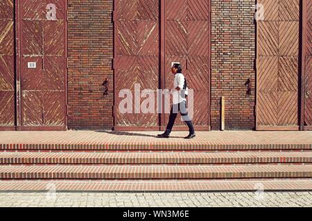 Side View Of Man Walking At Humboldt-umspannwerk On Sunny Day - Stock Photo