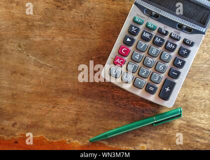 Directly Above Shot Of Calculator And Pen On Wooden Table - Stock Photo
