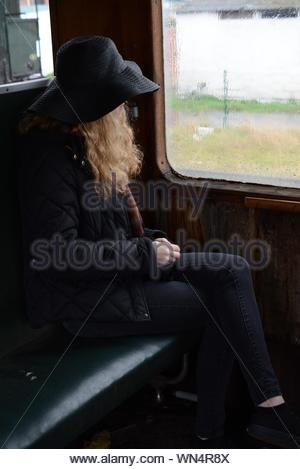 Woman Wearing Hat Sitting With Legs Crossed At Knee In Train - Stock Photo