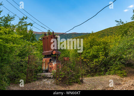 Old abandoned rusty electric transformer - Stock Photo