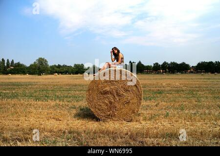 Woman Sitting On Hay Bale At Field Against Sky - Stock Photo