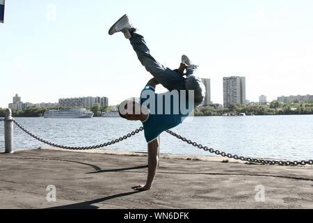 Man Breakdancing Against Lake - Stock Photo