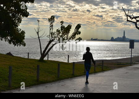 Rear View Of Woman Walking On Promenade Against Sky During Sunset - Stock Photo