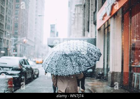 Rear View Of Man Walking On City Street In Snow - Stock Photo