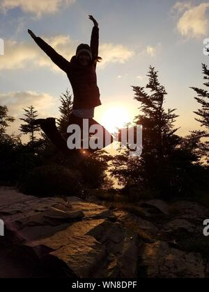 Young Woman Jumping During Sunset - Stock Photo