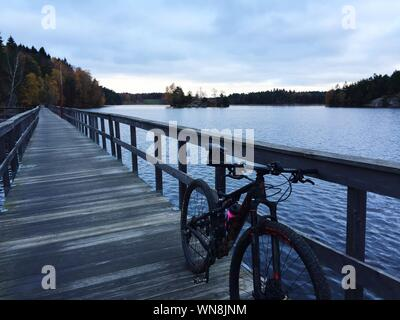 Bicycle Parked On Pier Over Lake Against Cloudy Sky - Stock Photo
