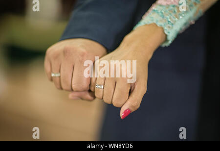 Cropped Hands Of Bride And Bridegroom Showing Wedding Rings - Stock Photo