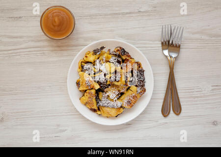 Homemade german Kaiserschmarrn pancake with apple sauce on a white wooden table, top view. Flat lay, overhead, from above. - Stock Photo