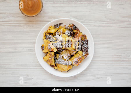 Homemade german Kaiserschmarrn pancake with apple sauce on a white wooden background, overhead view. Flat lay, top view, from above. - Stock Photo