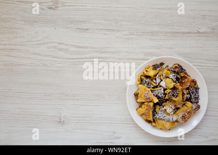 Homemade german Kaiserschmarrn pancake on a white plate on a white wooden background, overhead view. Flat lay, top view, from above. Copy space - Stock Photo