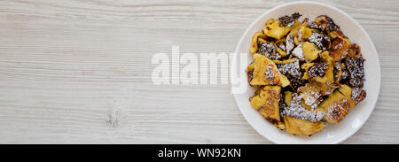 Homemade german Kaiserschmarrn pancake on a white plate on a white wooden surface, view from above. Flat lay, top view, overhead. Copy space. - Stock Photo