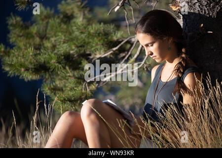 Chica adolescente leyendo un libro el exterior - Stock Photo