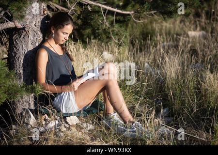 Chica adolescente leyendo un libro el exterior junto a un árbol - Stock Photo
