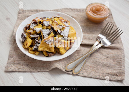 Homemade german Kaiserschmarrn pancake with apple sauce on a white wooden background, side view. Close-up. - Stock Photo