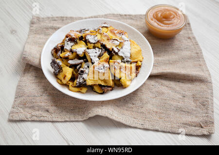 Homemade german Kaiserschmarrn pancake with apple sauce on a white wooden surface, side view. Close-up. - Stock Photo