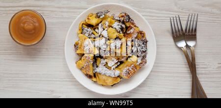 Homemade german Kaiserschmarrn pancake with apple sauce on a white wooden table, top view. Flat lay, overhead, from above. Close-up. - Stock Photo