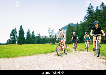 Family Riding Bicycle On Field - Stock Photo