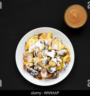 Homemade german Kaiserschmarrn pancake with apple sauce on a black surface, top view. Flat lay, overhead, from above. Close-up. - Stock Photo
