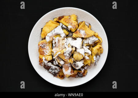 Homemade german Kaiserschmarrn pancake with apple sauce on a black background, top view. Flat lay, overhead, from above. Close-up. - Stock Photo