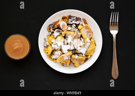 Homemade german Kaiserschmarrn pancake on a black background, top view. Flat lay, overhead, from above. - Stock Photo