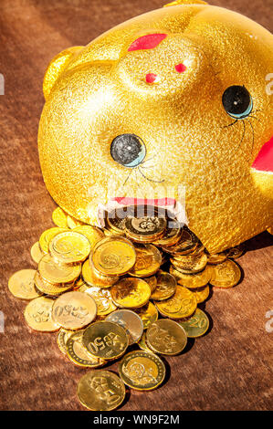 Close-up Of Coins Spilling From Broken Piggy Bank - Stock Photo