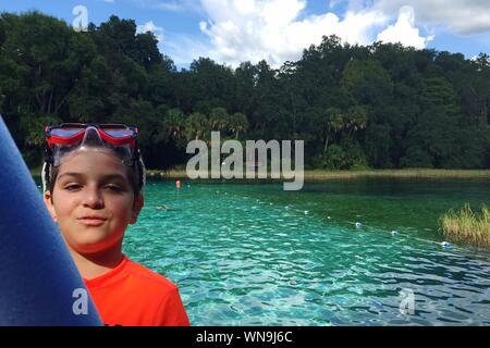 Portrait Of Smiling Boy Wearing Swimming Goggles Against Lake - Stock Photo