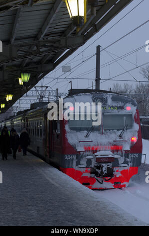 Vitebsky railway station,Saint Petersburg,Russia - January 24, 2019: Red-orange train covered with snow stands near the platform. Vertical orientation - Stock Photo