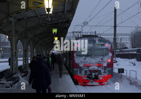 Vitebsky railway station,Saint Petersburg,Russia - January 24, 2019: Red-orange train covered with snow stands near the platform on which people are w - Stock Photo