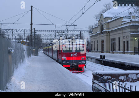 Vitebsky railway station,Saint Petersburg,Russia - January 24, 2019: The red-orange RZD train stands on the snow-covered track near the old building i - Stock Photo