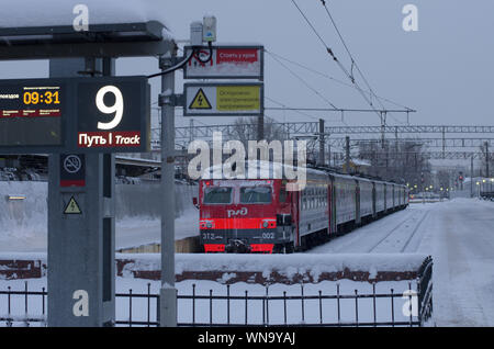 Vitebsky railway station,Saint Petersburg,Russia - January 24, 2019: Red-orange train covered with snow is on the 9th way it is indicated on the lumin - Stock Photo