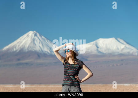 Portrait of young casual blond woman travel alone, caucasian girl in hat and sunglasses looking away with snow covered mountains on the background. St