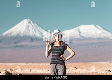 Young casual blond woman travel alone, caucasian girl in hat and sunglasses looking at camera with snow covered mountains on the background. Stunning