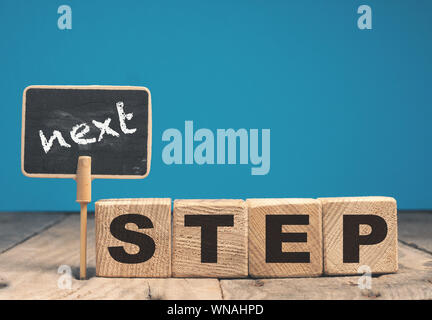 Wooden blocks and a chalkboard with the words Next step, motivation or career concept - Stock Photo