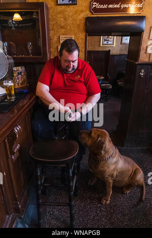 England, London, Southwark, Bermondsey, Male Customer Sitting at The Bar Of The Anchor Tap Sam Smiths Pub with Pet Dog - Stock Photo