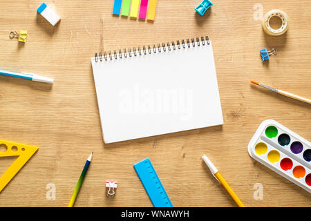 School notebook and various stationery on a wooden desk table. Back to school concept. Flat lay style composition, top view, overhead. - Stock Photo