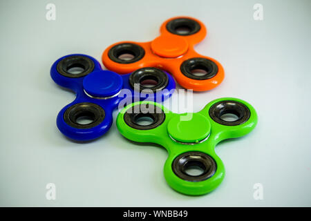 Close-up Of Colorful Fidget Spinners On White Table - Stock Photo