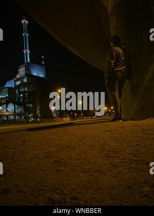 Rear View Of Man Leaning On Column Below Bridge At Night - Stock Photo