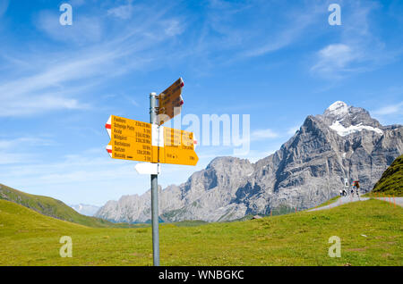 Yellow tourist sign in First, Switzerland giving distances and directions to hikers in the Swiss Alps. Popular hiking paths by Grindelwald leading to Bachalpsee. Summer Alpine landscape in background. - Stock Photo