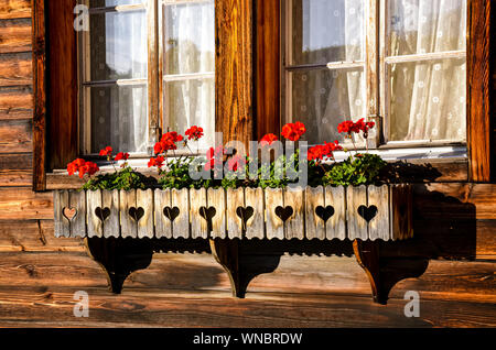 Typical red geranium flowers in the windows of traditional Alpine wooden chalets. Bavarian wooden hut. Flower decoration. Tradition, style. Bavaria, Austria, Swiss Alps. - Stock Photo