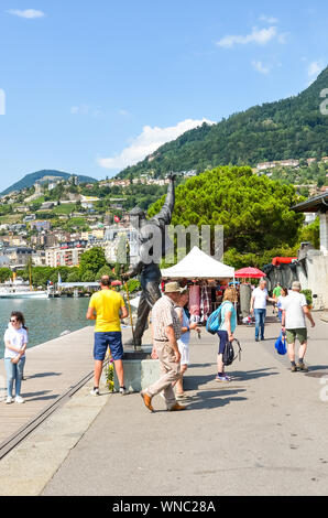 Montreux, Switzerland - July 26, 2019: People on the promenade by Geneva Lake around the statue of Freddie Mercury, lead singer of the famous band Queen. Tourists taking photos. Tourist attraction. - Stock Photo