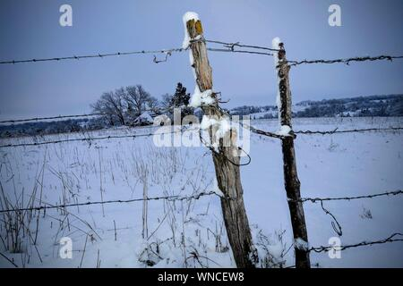 Fence By Snow Covered Field Against Sky - Stock Photo