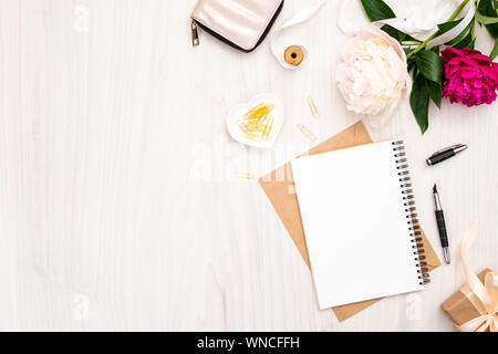 Flat lay home office desk. Female workspace with paper notebook, bouquet of pion flowers, golden accessories, purse on wooden background. Top view fem - Stock Photo