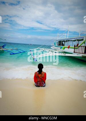 Rear View Of Teenage Girl Sitting On Shore At Beach - Stock Photo